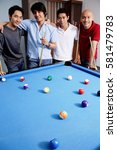Small photo of Men standing around pool table
