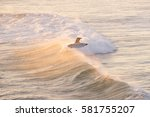 Surfing During The Sunset Off...