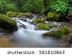 the flowing water of stream at... | Shutterstock . vector #581810863