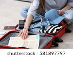woman packing her red suitcase... | Shutterstock . vector #581897797