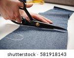 hands of seamstress cutting a... | Shutterstock . vector #581918143