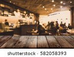 wood table top and blurred... | Shutterstock . vector #582058393