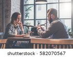 Small photo of One-on-one meeting. Two young business people sitting at table in cafe.Businesswoman using smartphone. Businessman makes photo on smartphone. On table is laptop and cup of coffee. Couple having dinner.