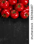 Small photo of Tomato on a black background with realistic reflection and water drops. Fresh tomatoes in a large amount
