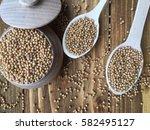 mustard seeds in a wooden bowl... | Shutterstock . vector #582495127