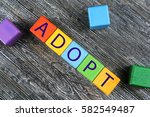 Small photo of Colorful cubes with word ADOPT on wooden background