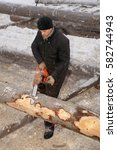 Small photo of Leningrad Region, Russia - February 2, 2010: Logger use chainsaw for cutting log.