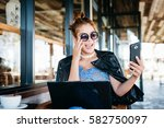 woman updating her snapchat in... | Shutterstock . vector #582750097