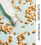 Small photo of Dairy alternative milk. Almond milk in glass bottle and fresh nuts over blue background, top view, selective focus. Clean eating, dairy-free, vegan, vegetarian, allergy-friendly, healthy food concept