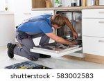 repairman examining dishwasher... | Shutterstock . vector #583002583