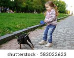 Stock photo girl in a pink striped blouse and blue jeans pulling dog 583022623