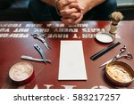 Small photo of Blank card with barber tools on table free space. Side view on gules workplace with hairstyling instruments and hands of sitting man on background, Work, barbershop, manhood concept