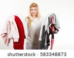 Small photo of Fashion, clothes dilemmas concept. Woman holding big pile of warm winter clothing, cant decide what to wear, on white grey