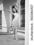 Small photo of ballerina on the street in a ballet position