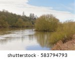 Small photo of A lone canoeist looking very small as he paddles down a tree lined River Trent