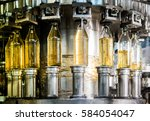 filling bottles with juice | Shutterstock . vector #584054047