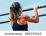 female doing pull ups in... | Shutterstock . vector #584252563