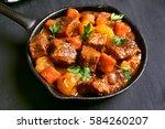 beef stew in frying pan on... | Shutterstock . vector #584260207