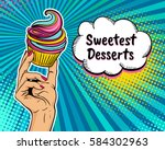 Pop art background with female hand holding bright cupcake and  speech bubble with Sweetest Desserts text. Vector colorful hand drawn illustration in retro comic style. | Shutterstock vector #584302963