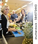 Small photo of Confident Cashier Holding Juice Packet At Checkout Counter In Su