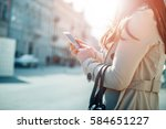 young woman walking and using a ... | Shutterstock . vector #584651227
