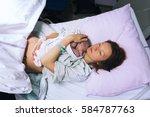 mother holding her newborn baby ...   Shutterstock . vector #584787763