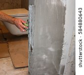 Small photo of Man's hand with spatula in the repair room. Plasterer worker aligns wall plaster or lime.