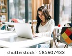 brunette studying on laptop and ... | Shutterstock . vector #585607433