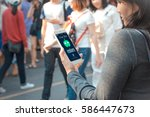 Small photo of chat bot concept.Young Female hands holding mobile phone on blurred people walking as background
