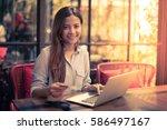 asian woman drinking coffee in... | Shutterstock . vector #586497167