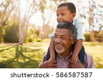 grandfather carries grandson on ... | Shutterstock . vector #586587587