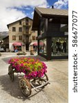 Small photo of LIVIGNO, ITALY - AUGUST 1: Wain with flowers in front of fashion shops on streets of duty-free area on 1 August 2016 in Livigno, Italy.