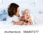mother and child on a white bed.... | Shutterstock . vector #586807277