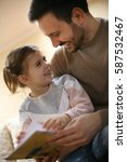 father reading a story to his... | Shutterstock . vector #587532467