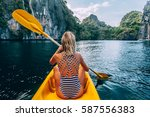 Woman Paddling A Kayak In The...