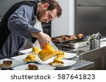 Small photo of Chef pours a gamy sauce on plate