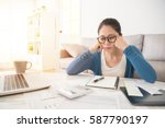Small photo of sad beautiful mixed race asian chinese woman looking at unpaid bills feel distressed sitting on sofa in the living room at home. interior and domestic housework concept.