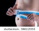 Fat man with tape-measure isolated over a black background.