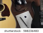 Small photo of Acoustic and electric guitars, studio earphones and musical leaf