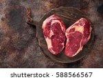 Small photo of Raw fresh meat Ribeye Steak heart shape heart shape on brown rusty background