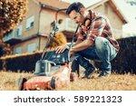 man cutting grass in his yard... | Shutterstock . vector #589221323