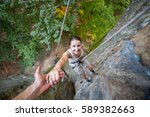 man rock climber is helping to... | Shutterstock . vector #589382663