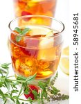 Iced tea accompanied by mint, raspberry, lemon and lime - stock photo