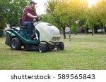 gardener cutting the grass of a ... | Shutterstock . vector #589565843