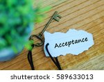 Small photo of Key and torn paper with word acceptance on wooden background.