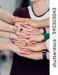Small photo of Shot of a group of unrecognizable coworkers' hands in a huddle