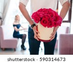 Stock photo man holding a gift bouquet of red roses for the girls the composition of flowers in white hatbox 590314673