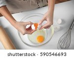 Small photo of Woman cracking eggs into glass bowl