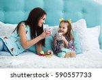 mother and daughter drink tea... | Shutterstock . vector #590557733