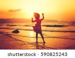 happy girl jumping at the beach ... | Shutterstock . vector #590825243